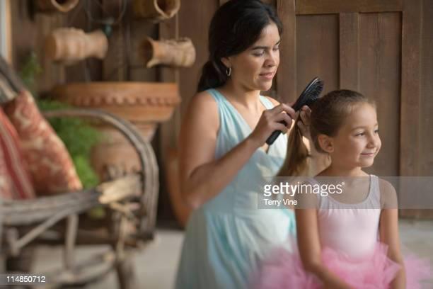 Mother brushing ballerina's hair
