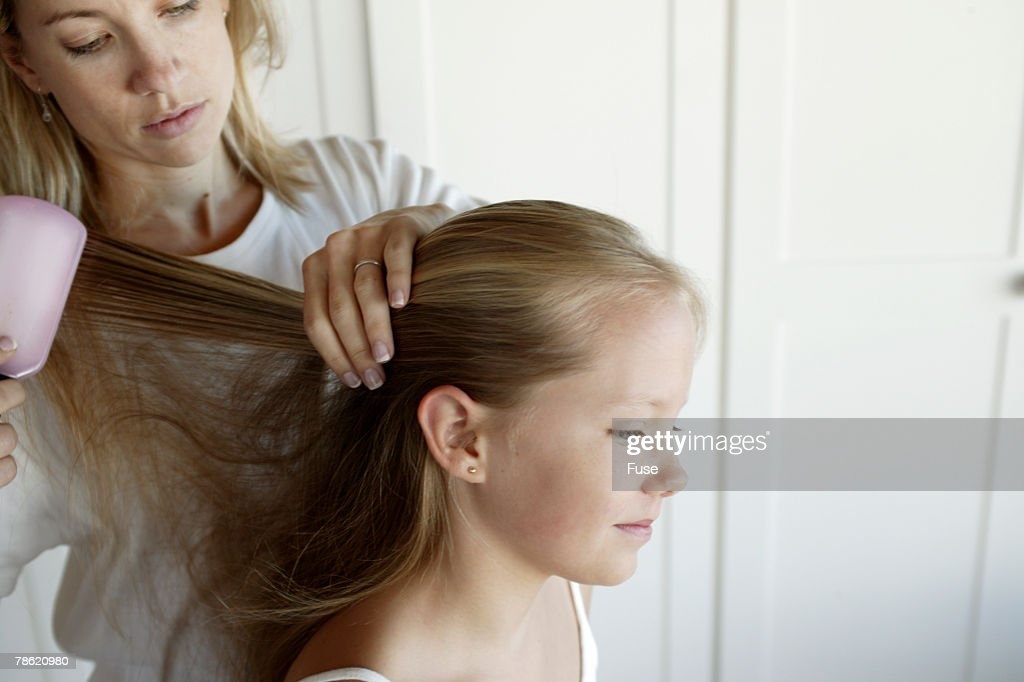 Mother Brushing Daughters Hair