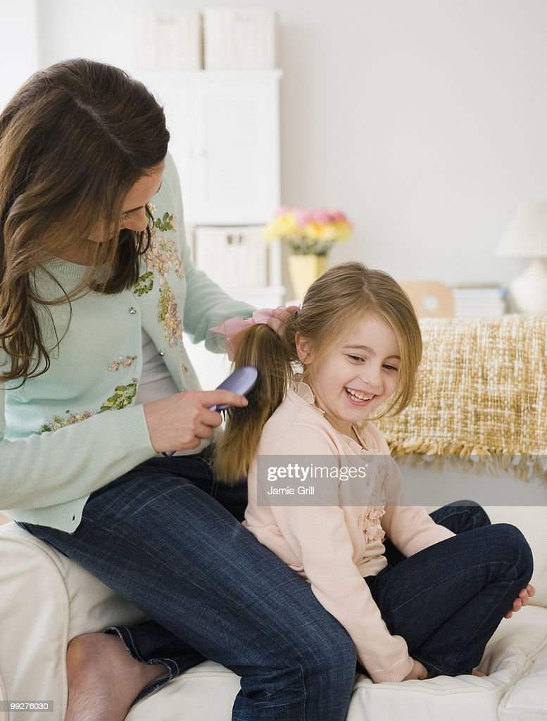 Mother brushing daughter's hair