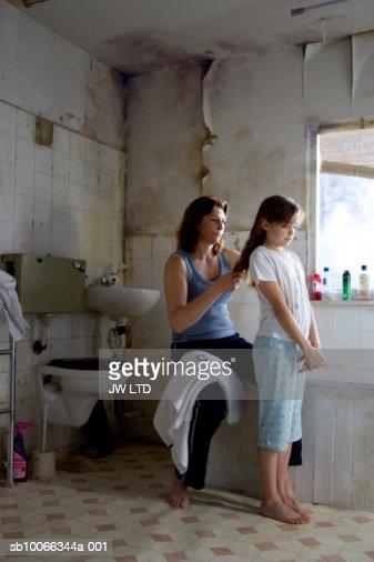 Mother brushing girls hair in bathroom