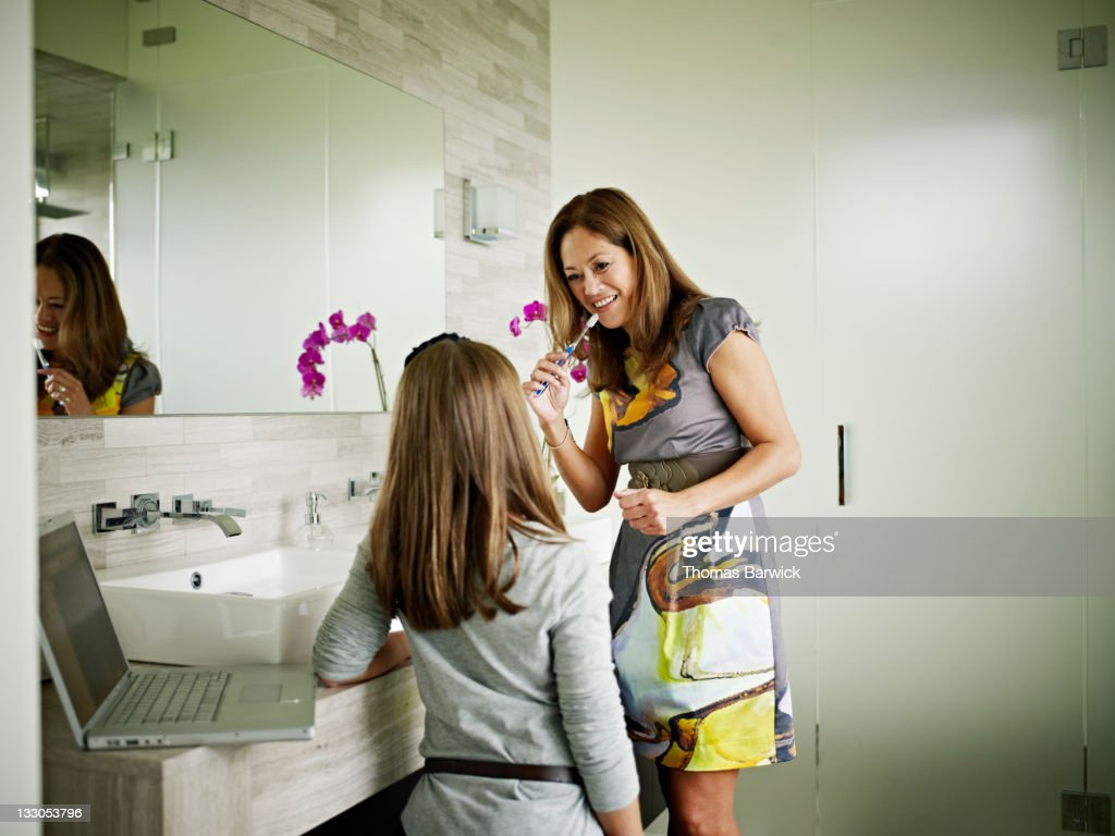Mother brushing teeth in bathroom with daughter
