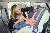 Mother buckling baby in car seat