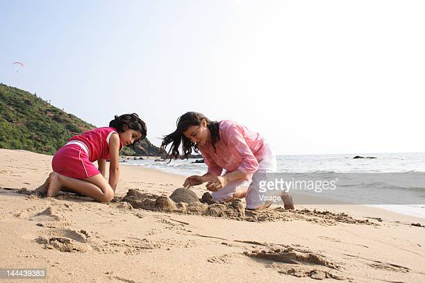 A mother building a sandcastle with her daughter