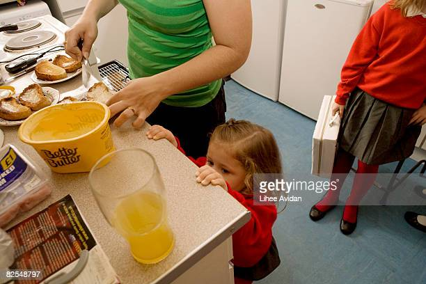 Mother buttering toast while two girls watch