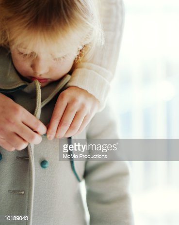 Mother buttoning daughter's jacket