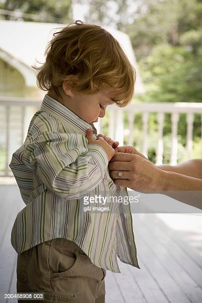 Mother buttoning male toddler's (21-24 months) shirt on porch