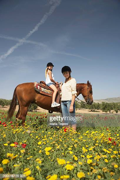 Mother by daughter (9-11) on horse, portrait, low angle view