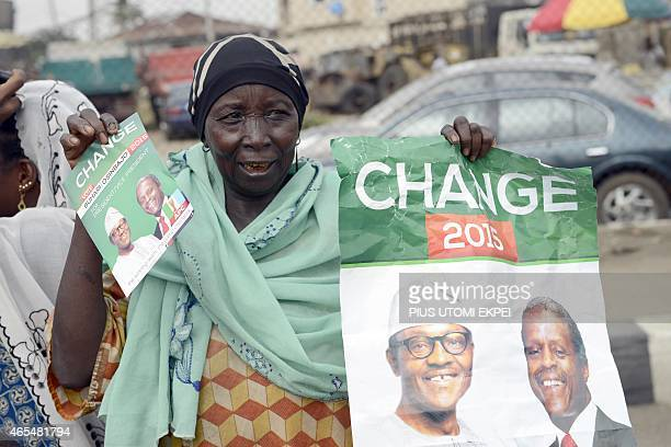 A mother carries banner to drum support for the leading opposition All Progressives Congress presidential candidate Mohammadu Buhari and running mate...