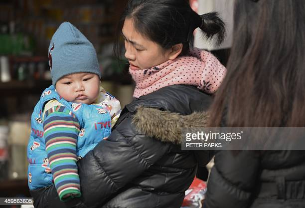A mother carries her baby on a street in Shanghai on December 28 2013 China's top legislative committee formally approved a loosening of the...