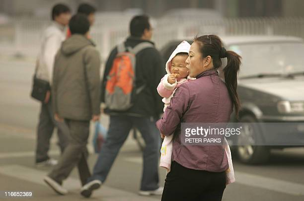 A mother carries her baby on the street in Beijing 06 November 2007 More than half of Beijing's young adults born into onechild families want only...