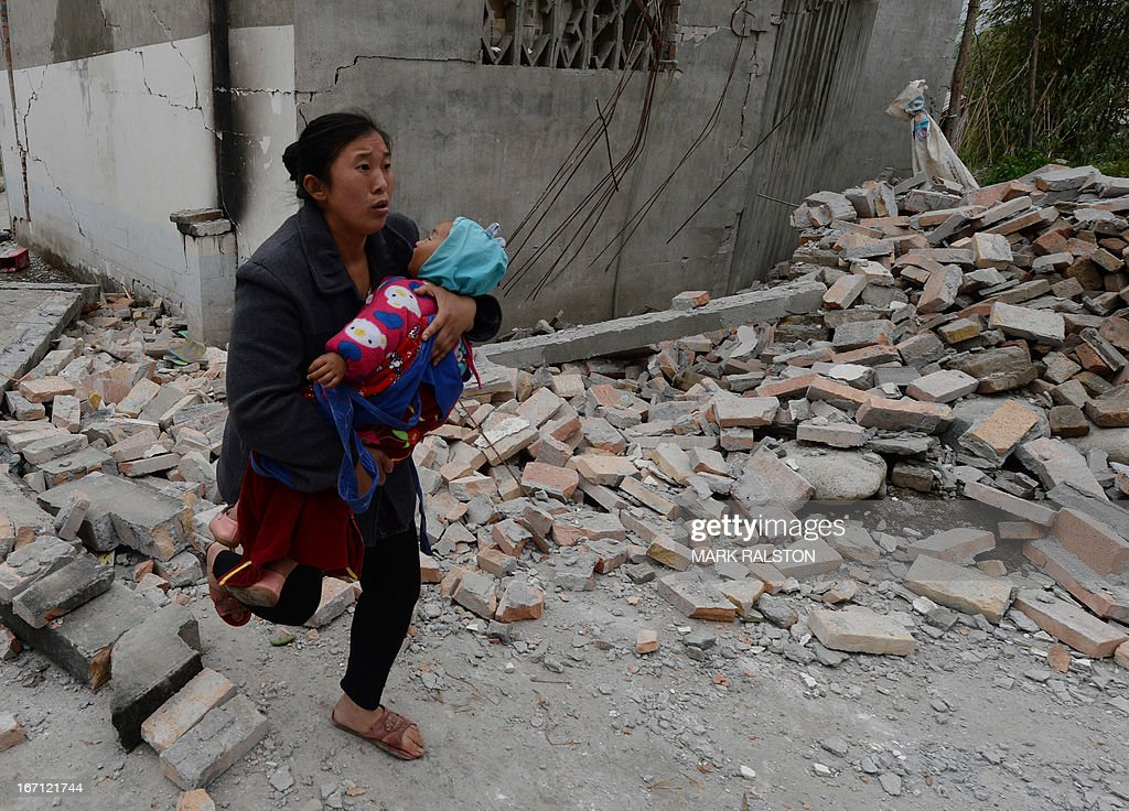 A mother carries her baby through rubble after a magnitude 7.0 earthquake hit Lushan, Sichuan Province on April 21, 2013. More than 150 people were killed and 3000 injured when a strong earthquake shook southwest China, wrecking homes and triggering landslides in an area devastated by a major tremor in 2008. AFP PHOTO/Mark RALSTON