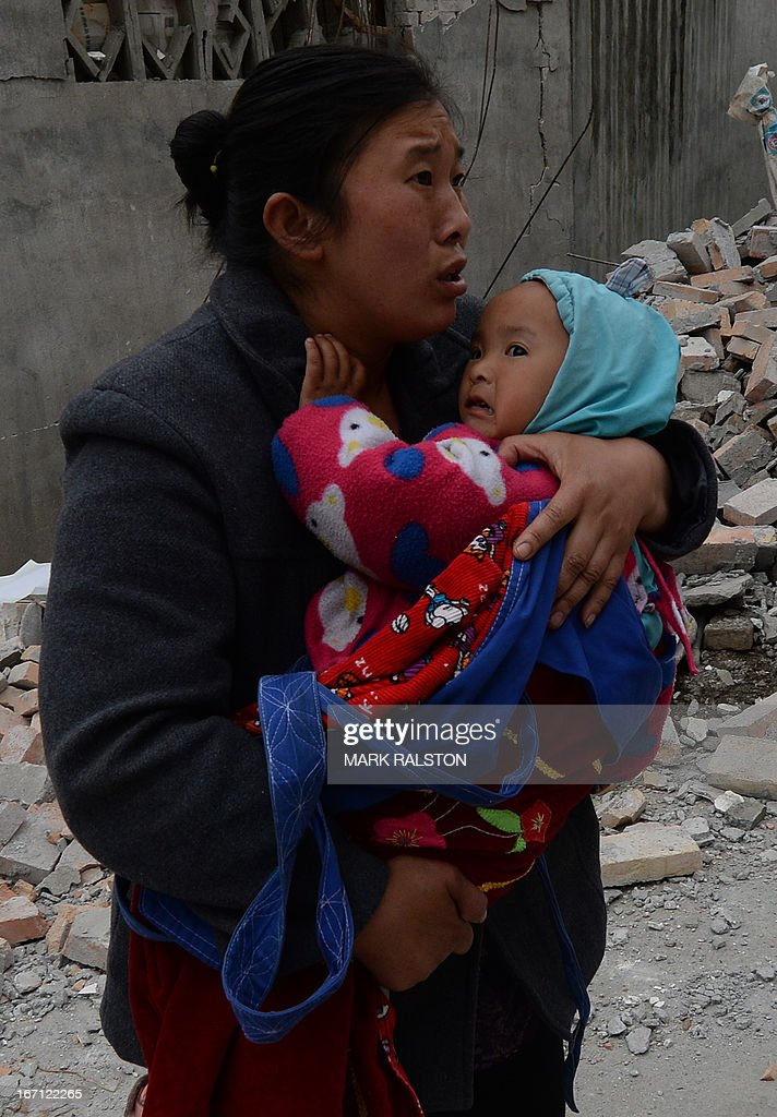 A mother carries her baby through rubble after a magnitude 7.0 earthquake hit Lushan, Sichuan Province on April 21, 2013. More Thousands of rescue workers combed through flattened villages in southwest China in a race to find survivors from a powerful quake as the toll of dead and missing rose past 200. AFP PHOTO/Mark RALSTON