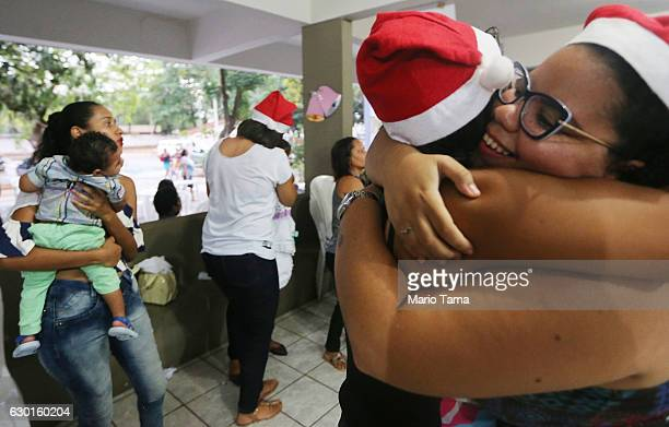 A mother carries her baby who has microcephaly as volunteers hug during a Christmas party on December 17 2016 in Recife Brazil The party was thrown...