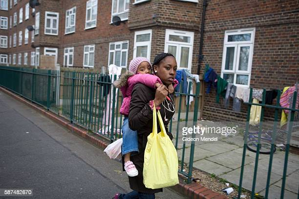 A mother carries her daughter home after a long day at work She had just picked up her child from a nursery and was walking back to her home in the...