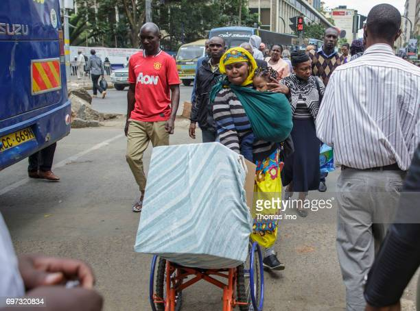 A mother carries her daughter in a baby sling while transporting a box on a wheelchair Street scene in Nairobi capital of Kenya on May 15 2017 in...