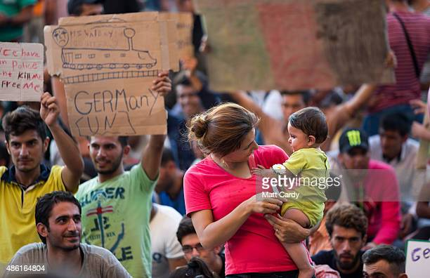 A mother carries her infant girl as migrants protest outside Keleti station in central Budapest after it was closed to migrants earlier today on...