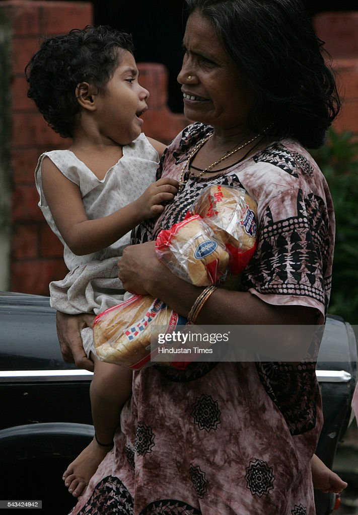 Mother carry bread packets in a flood affected kalina on tuesday. Mumbai returned to normalcy after week long of heavy rains on August 2, 2005 in Mumbai, India.