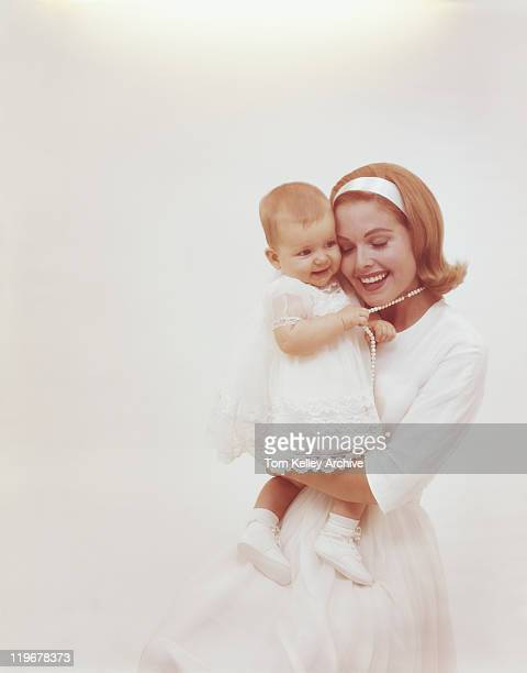 Mother carrying baby girl against white background