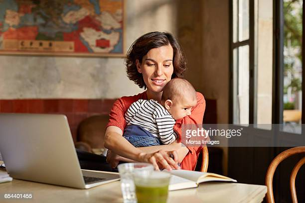 Mother carrying baby while reading book at table