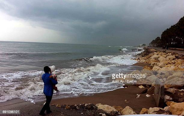 Mother Carrying Child On Seashore Against Cloudy Sky