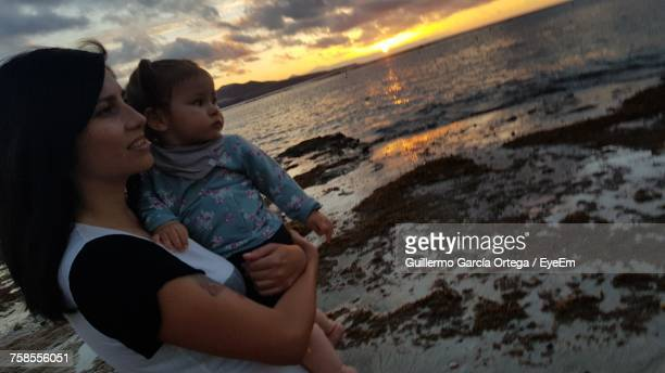 Mother Carrying Cute Daughter While Standing On Shore At Beach