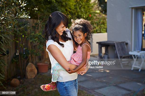 Mother carrying daughter & both laughing