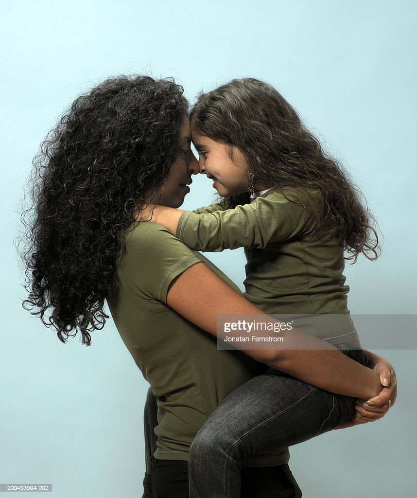 Mother carrying daughter head to head, side view