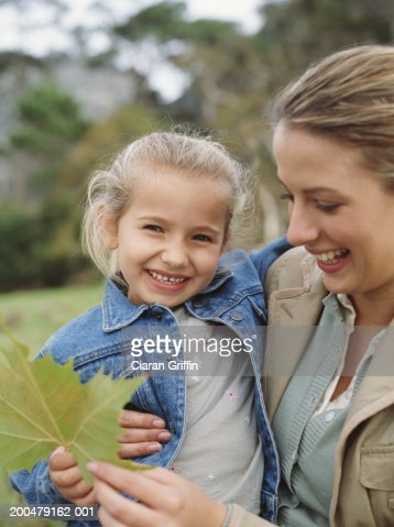 Mother carrying daughter (4-6) in field, holding leaf, smiling : Stock Photo