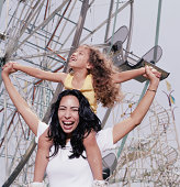 Mother carrying daughter (3-5) on shoulders at amusement park, smiling