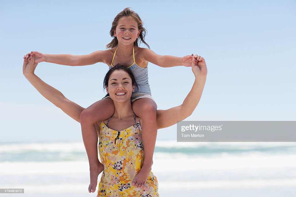 Mother carrying daughter on shoulders : Stock Photo