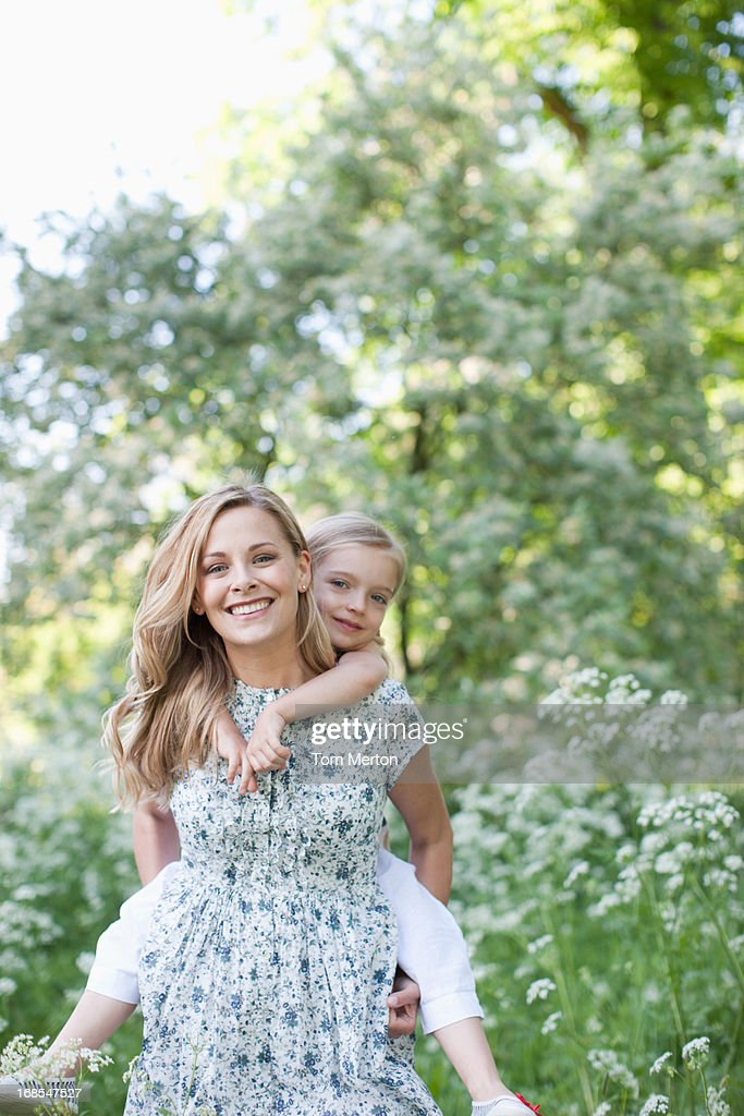 Mother carrying daughter outdoors