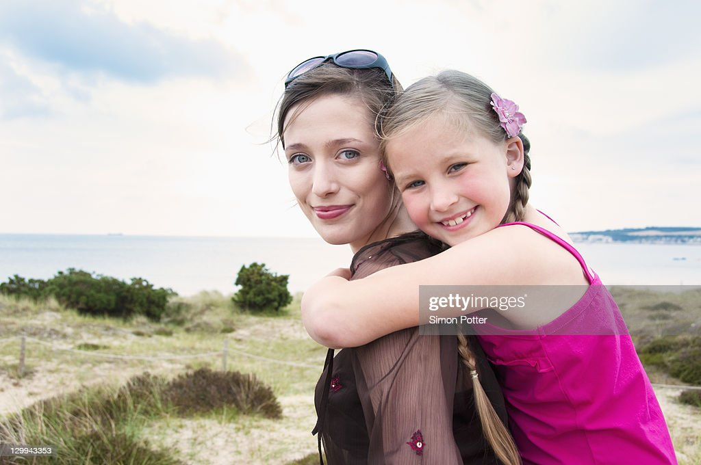 Mother carrying daughter piggy back : Stock Photo