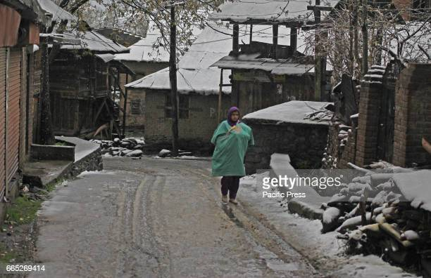 A mother carrying her baby inside the Kashmiri traditional dress Phiran walking on the road in Tral area of South Kashmirs Pulwama district in Indian...
