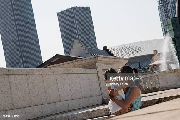 A mother carrying her child goes down stairs at Dalian's 'City of Water' with high rise buildings in the background The City of Water also dubbed...