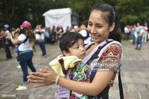 A mother carrying her child performs during the 'Big Latch On' breastfeeding festival held at the Bonatic Garden of the Chapultepec Park in Mexico...