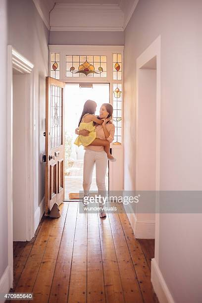 Mother carrying her daughter into the hall of their home