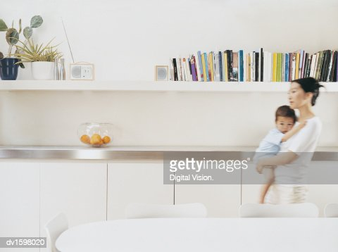 Mother Carrying Her Young Son Through Her Dining Room : Stock Photo