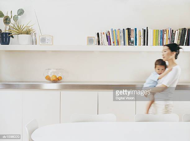 Mother Carrying Her Young Son Through Her Dining Room