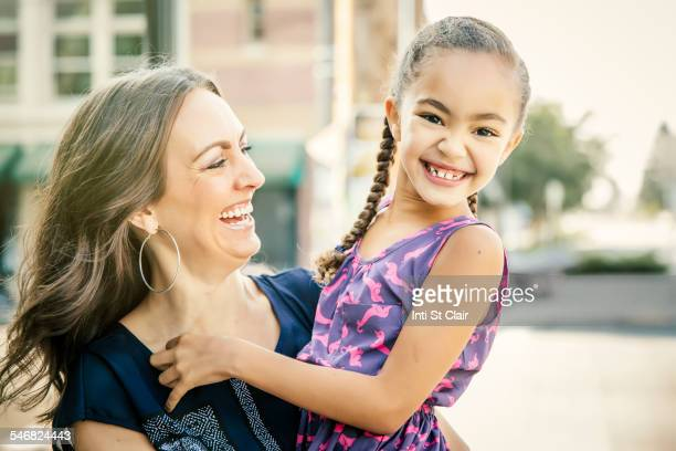 Mother carrying smiling daughter outdoors