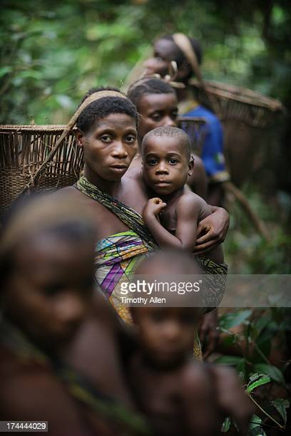 Mother carrying son in a sling in the jungle