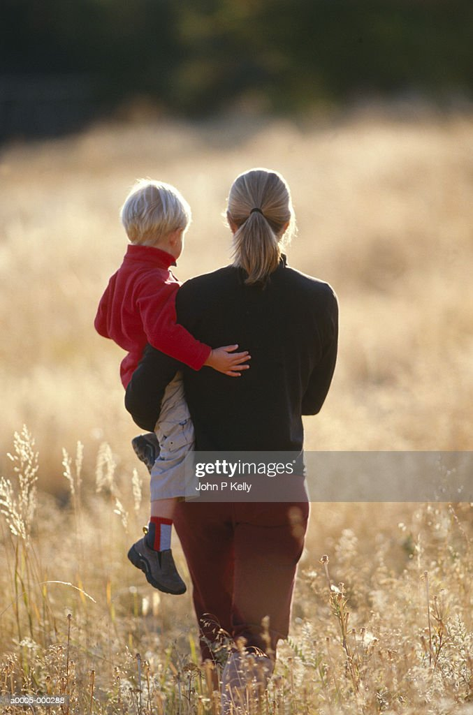 Mother Carrying Son in Field : Stock Photo