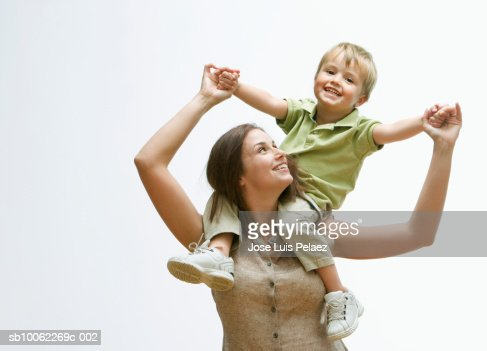 Mother carrying son (3-4) on shoulders, smiling : Stock Photo