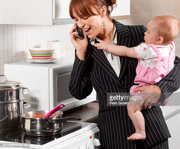 Mother carrying son (6-11 months) , using mobile phone