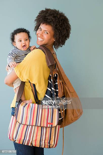 Mother carrying three bags and baby son