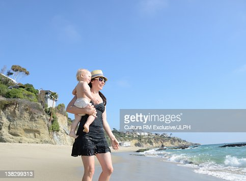 Mother carrying toddler on beach : Stock Photo