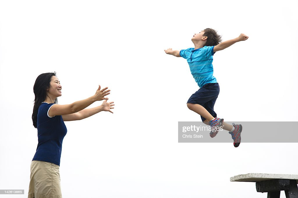 Mother catching her son jumping into her arms