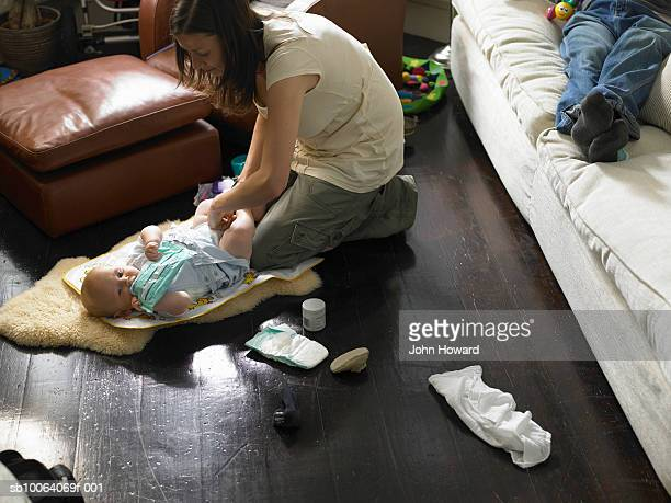 Mother changing baby boy (9-12 months) on floor, father on sofa