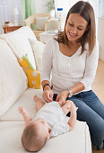 Mother changing baby's diaper on sofa