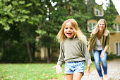 Mother chasing cheerful girl outdoor. Focus is on girl in the front.