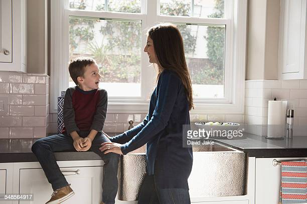Mother chatting to son sitting on kitchen counter